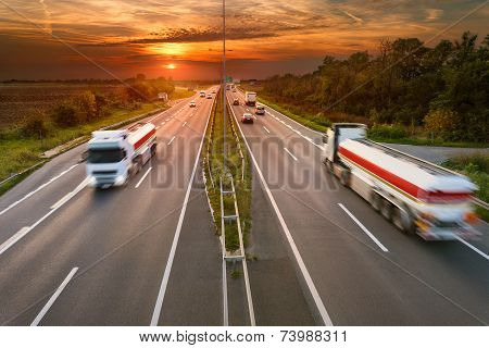 Two White Trucks In Motion Blur On The Highway