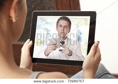 Woman having video chat with doctor on laptop at home