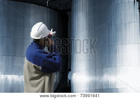 refinery worker in hard-hat pointing at industrial fuel and oil tanks