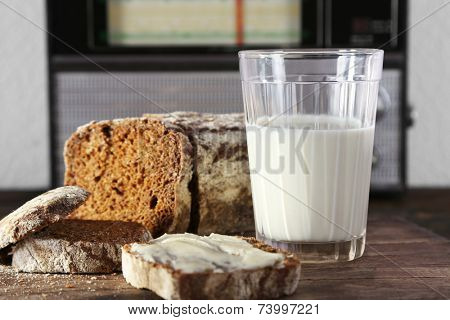 Rye bread and glass of milk on wooden cutting board on wooden table on radio set and light wall background