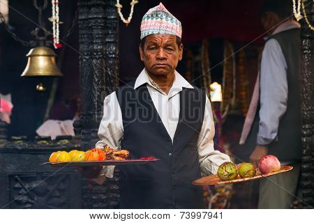 BHAKTAPUR, NEPAL, NOVEMBER 24, 2010: Goat sacrifice ritual: A man looking possessed is holding fruit plates covered with blood from the animal in Bhaktapur, Nepal