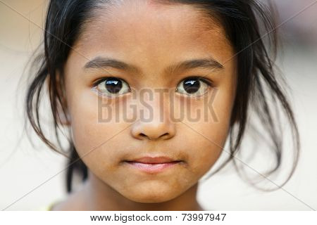 BHAKTAPUR, NEPAL, NOVEMBER 24, 2010: Close portrait of a Nepalese little girl posing in the main Bhaktapur square