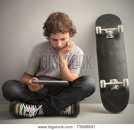 teenager sitting on skateboard with tablet pc