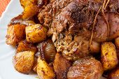 picture of frizzle  - a tasty roast with baked potatoes on a table with a tablecloth orange - JPG