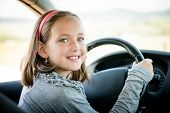 pic of steers  - Child pretends driving car sitting on front driver seat with hands on steering - JPG