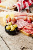 stock photo of charcuterie  - Charcuterie assortment and olives on wooden background - JPG