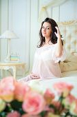 foto of negligee  - Beautiful pregnant girl in a lace negligee sitting on a bed of roses and touching hair - JPG