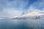 image of tromso  - Snowy mountains along a fjord in northern Norway Tromso region - JPG