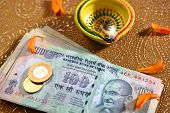 stock photo of laxmi  - 100 rupee bank notes and coins with indian traditional lamp - JPG