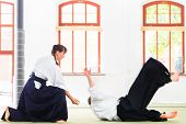 stock photo of aikido  - Man and woman fighting at Aikido training in martial arts school  - JPG