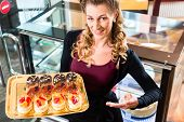 image of confectioners  - Female confectioner presenting tray of cake in bakery or pastry shop - JPG