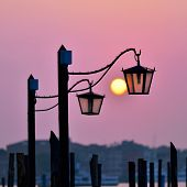 stock photo of risen  - Venice at sunrise lampposts at San Marco squareand risen sun on background Venice Italy - JPG