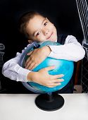 stock photo of 7-year-old  - seven year old school boy sitting by the table with a globe - JPG