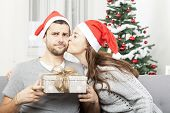 image of sad christmas  - man is skeptical about christmas gift while his girlfriend gives him a kiss