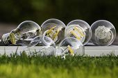 stock photo of diodes  - various E27 bulbs LED halogen and tungsten bulb on solar panel some on the grass  - JPG