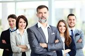 stock photo of united we stand  - Happy business team with arms crossed at the office - JPG