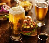 stock photo of gourmet food  - beer being poured into glass with gourmet hamburgers - JPG