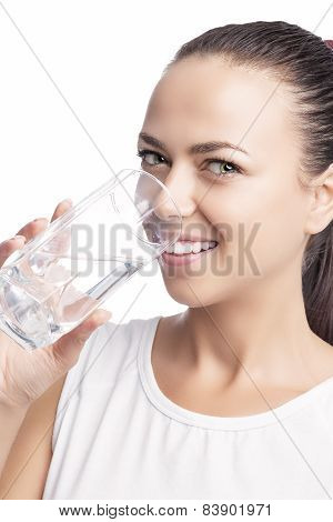 Portrait Of Happy Smiling Caucasian Brunette Woman Drinking Clear Water From Glass