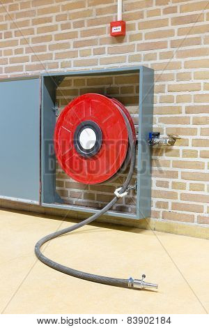 Fire hose on red reel at wall
