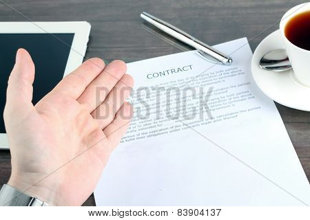 Man Sitting In A Table Showing, Offering  A Contract And Where The Signer Must Sign