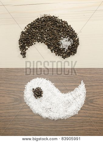 Salt and pepper on wooden background as yin and yang