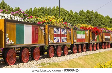 colorful floral train with flags of different countries in a park