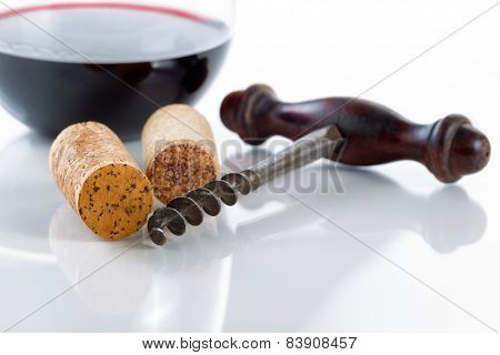 Old Corkscrew With Corks And Red Wine In Glass On Table