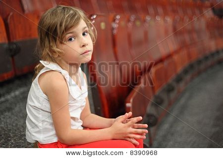 Little Girl Sitting On Stair Near Armchairs In Circus And Looking At Camera