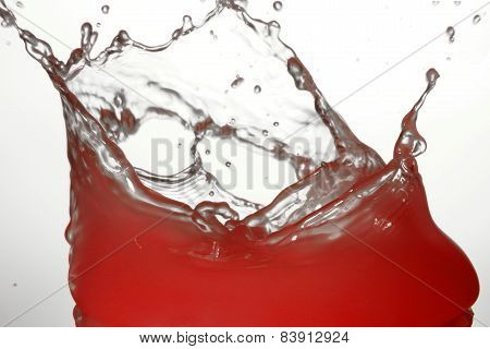 Red water splashing on light background, fluttering drops of water