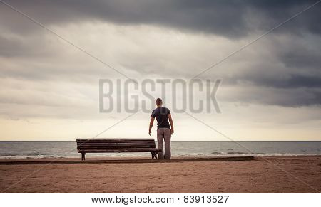 Tired Young Man Goes To The Old Wooden Bench