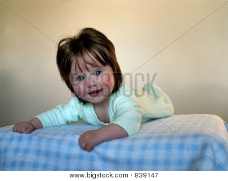 Cute smiling baby girl on the blanked