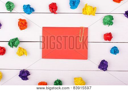 A note on white wooden background with colorful crumpled paper
