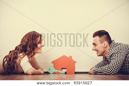 Couple Lying On Floor Daydreaming At Home