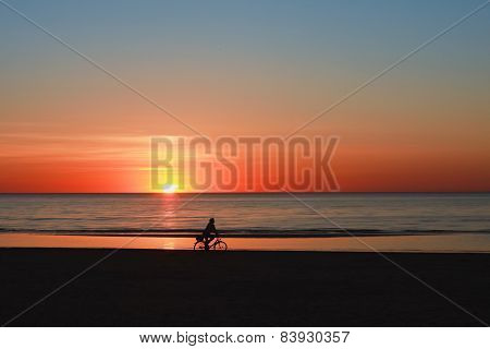 Silhouette of a cyclist on the beach at sunset