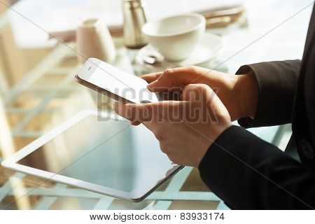 Businesswoman Texting With Her Mobile During A Coffee Break