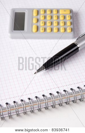 Business Concept - Note Book With Checked Pages, Pen And Calculator