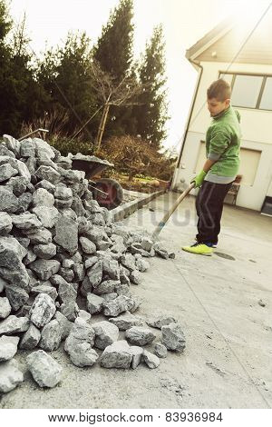 child with shovel helping to take gravel away
