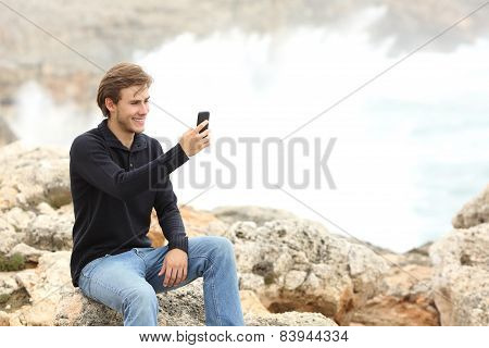 Man Using A Smart Phone In Winter On The Beach