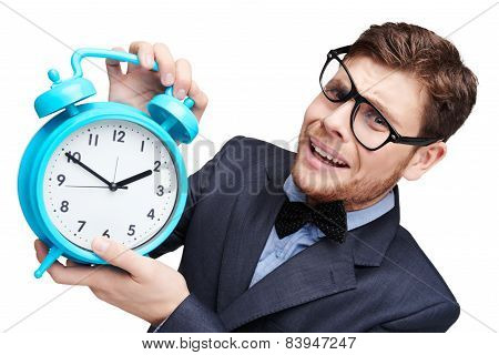 Young afraid man holding alarm clock