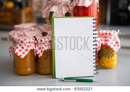 Closeup On Notepad Among Jars With Homemade Fruits Jam And Pickl