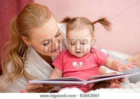 happy mother reads a book to baby girl