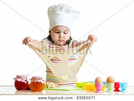 Little girl in cap of the cook playing with dough