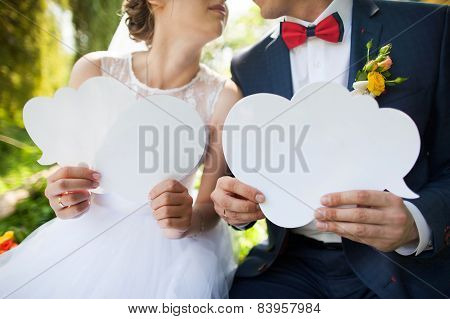 Bride and groom holding blank clouds for dialogue, close-up