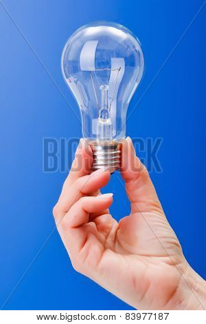 Hand Holding A Clear Incandescent Light Bulb