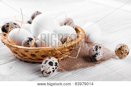 Quail and chicken eggs in a wicker basket on a wooden board