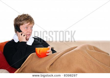 Woman telephoning on Couch with a Cup of Tea