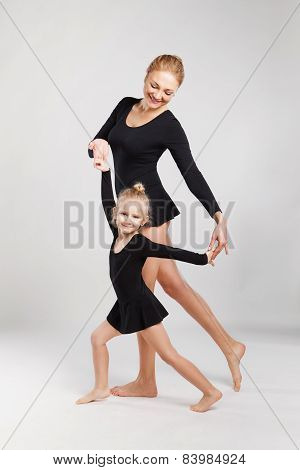 Mom teaching daughter dancing. Daughter  and mother are gymnastics