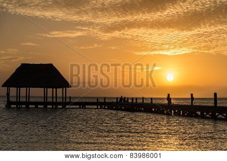 Couple In Love At A Wooden Pier Palapa Enjoying Sunset At Holbox Island Near Cancun, Traveling Rivie