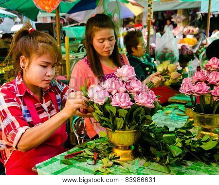 Young women create floral arrangements at an outdoor market