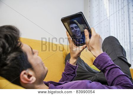 Handsome young man taking selfie or video chatting with tablet PC